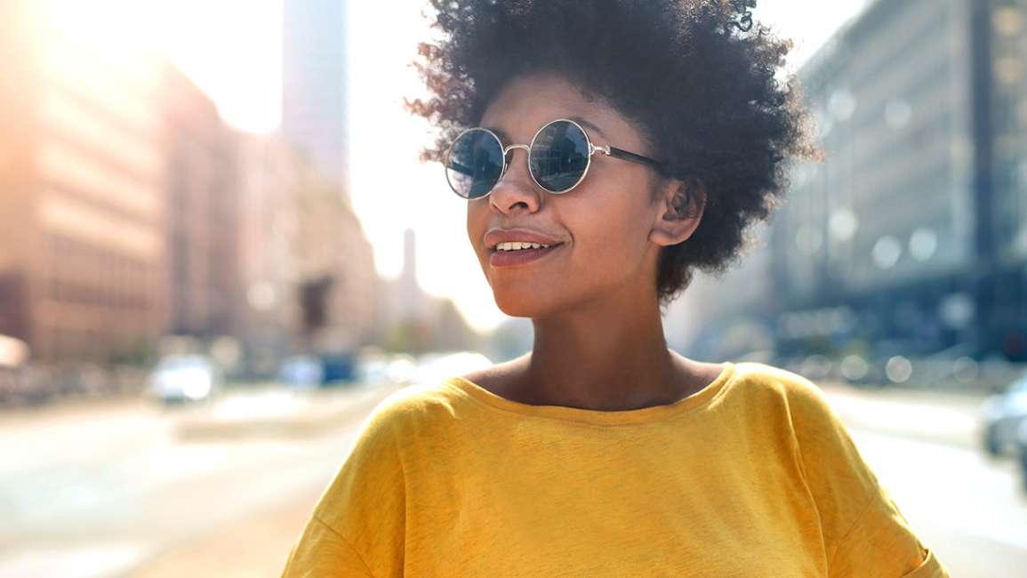 Người phụ nữ đeo kính mắt, mặc áo vàng đang mỉm cười trên phố